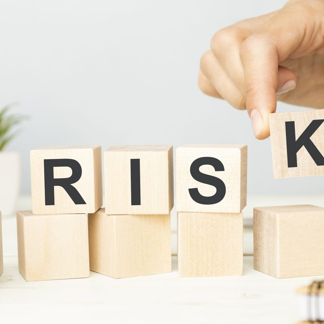 RISK word written on wooden cubes. Financial risk assessment, risk reward and portfolio risk management concept. Financial graphs and charts background